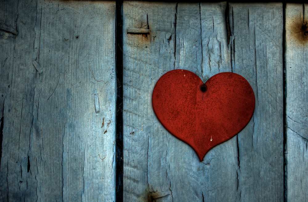 red metal heart on wood background